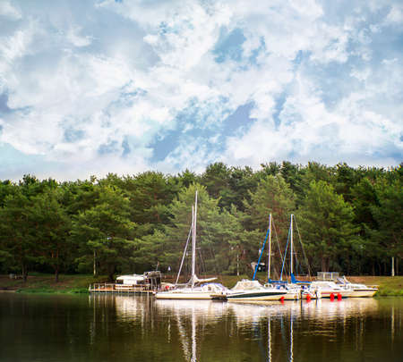 Boats and yachts in a water near the shore with pine trees on a cloudy day. Kaunas, Lithuania., lithuania