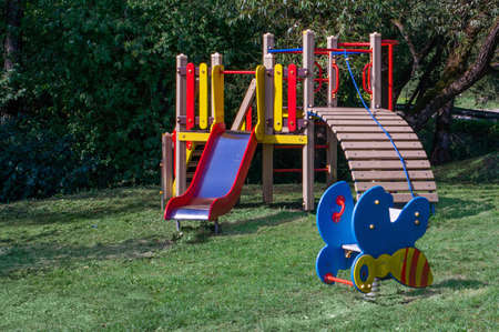 Colorful wooden playing equipment for children in a park on sunny day