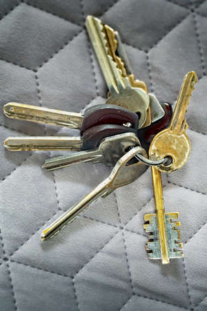 Old various worn keys bound by a metal ring on a grey cloth background. Close up. Foto de archivo - 129647383