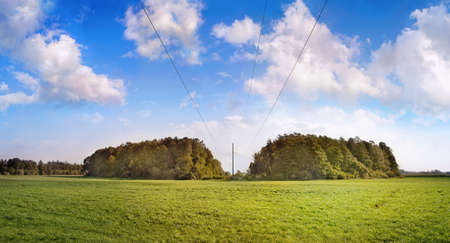 Panoramic view of high voltage line between two forest groups at the edge of the forest on cloudy day. Banque d'images - 130691822