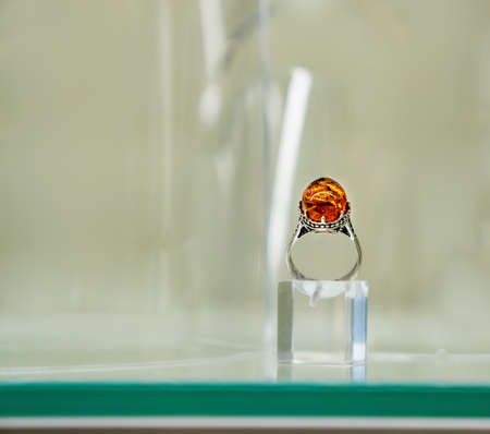 Silver ring with amber eye on a glass shelf. Close up