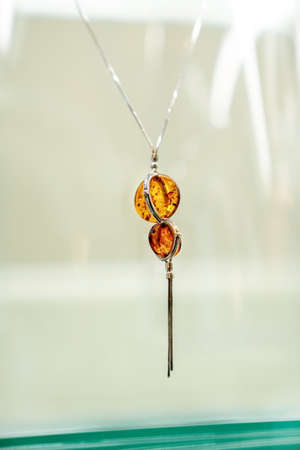 Silver necklace with amber on glass shelf. Close up.