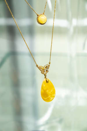 Golden necklace with amber and small diamonds on a glass shelf. Close up.
