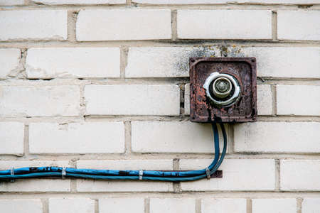 An old rusty lamp with a broken bulb with blue wires on a white brick wall. Close view.