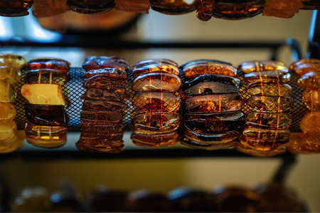Amber bracelets on a special shelf. Close up. Imagens