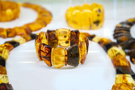 Amber neklaces and bracelets on a white background. Close up.