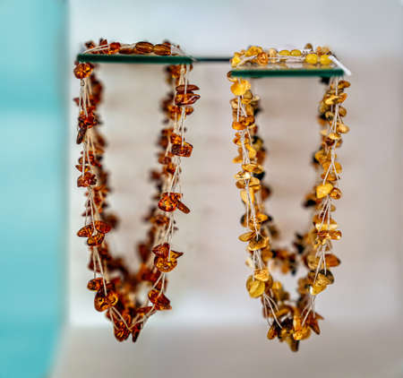 Amber neklaces on a glass shelfs. Close up. Imagens