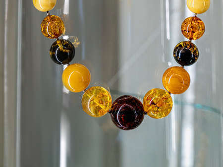 Amber neklace on a glass shelf. Close up.