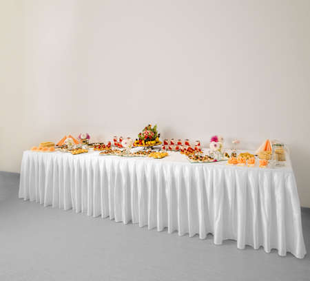 Large festive table with a white tablecloth and a banquet on it.