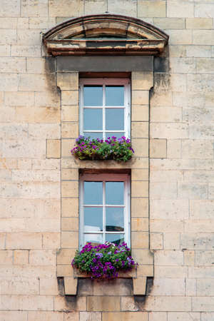 Two windows with flowers in the old house. Belgium.