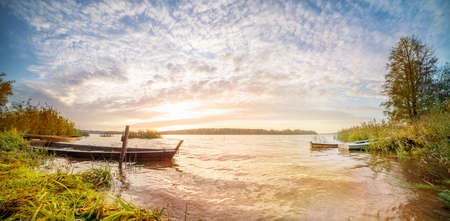 Panoramic landscape with sunrise in a water body with boats in autumn