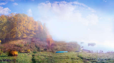 Panoramic autumn landscape with boats on a water body shore in a hazy morning. Imagens