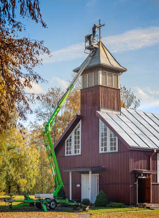 Repair of wooden church tower cross. A man standing in the aerial lift and repairing the cross. Imagens