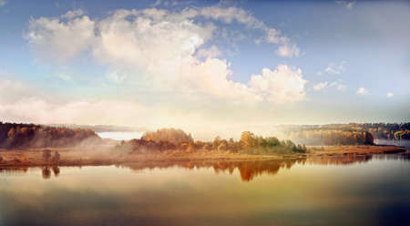 Panoramic autumn landscape of water body in foggy morning