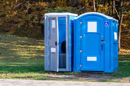 Two portable toilets in a park.One of them for disabled. Imagens