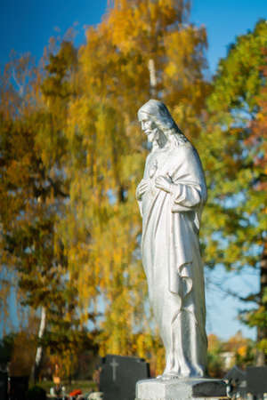 Concrete statue of Jesus Christ painted with silver paint in cemetery in autumn. Stok Fotoğraf