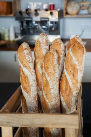 Fresh baguettes in a wooden basket. Close view.