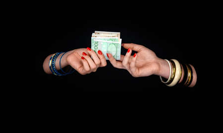 Two womens hands with bracelets pass each other the euro currency. On a black background. Stok Fotoğraf