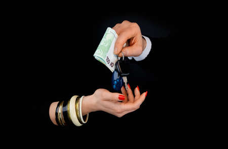 Mens hand giving to  womans hand euro banknotes and car keys  in a black background Stok Fotoğraf
