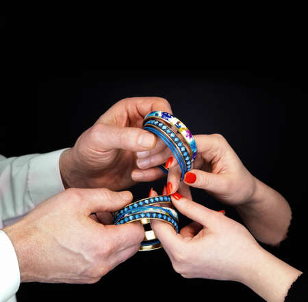 Mens and  womans hands holding blue bracelets on a black background