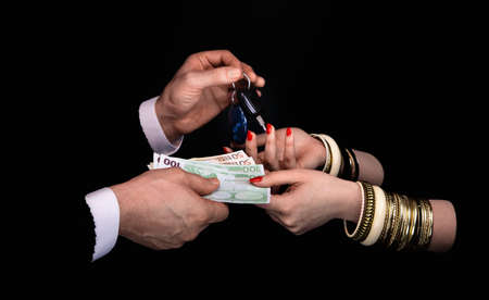 Mens hands giving to  womans hands euro banknotes and car keys  in a black background