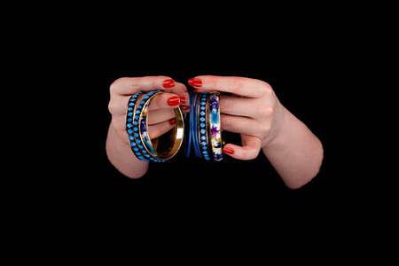 Blue bracelets in womans hands on a black background. Close up.
