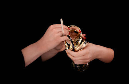 Two caucasian womans hands with golden bracelets on a black background. Zdjęcie Seryjne - 133090192