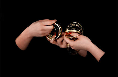Two caucasian womans hands with golden bracelets on a black background.