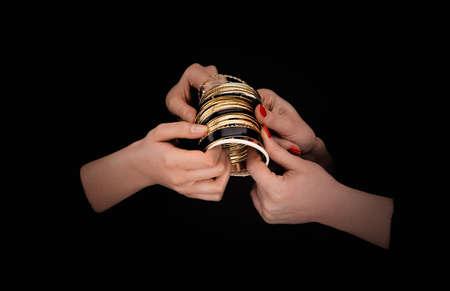 Two caucasian womans hands with golden bracelets on a black background. Zdjęcie Seryjne - 133091174