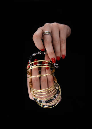 Womans hands with golden bracelets and a ring on a black backround. Zdjęcie Seryjne - 133093826