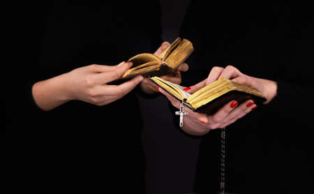 Two women read the bible and showing with a finger at the book page. On a black background. Stockfoto