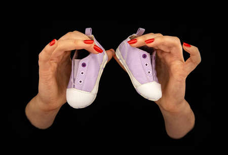 Woman's hands holding two baby shoes on a black background. Close up.