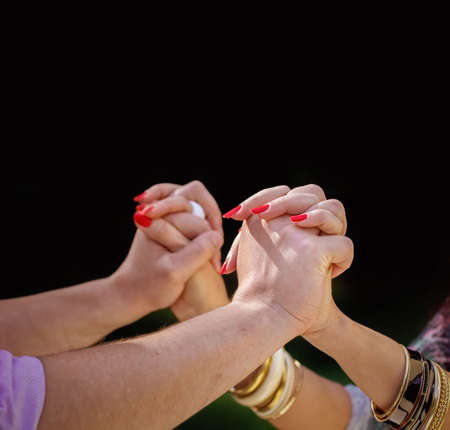 Males hands holding females hands with red nails, rings, and golden bracelets. On a black background