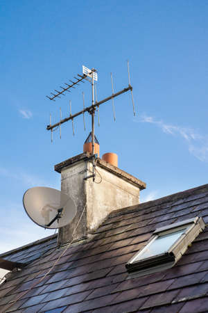 Many various antennas on a house chimney. Banque d'images