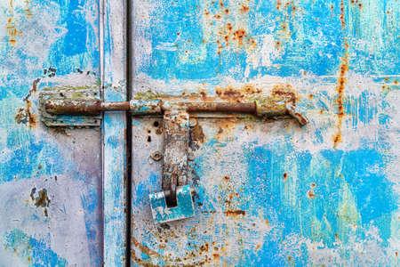 Blue padlock on a rusty metallic blue door. Close view.
