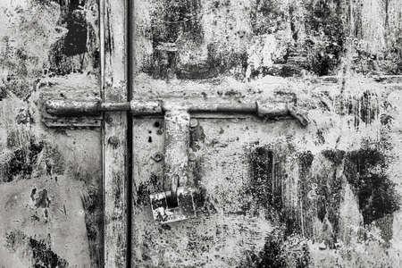 Padlock on a rusty metallic dirty door. Close view. Black white