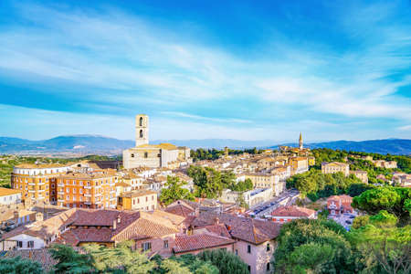 Panorama of Perugia, Italy under a blue and partly cloudy sky. San Domenico cathedral in left of frame. Also seen are other churches, bell towers, and rooftops of the town, with green hills and mountains in the distance. Assisi visible on the mountain in left.