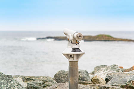 The coin-operated monocular for tourists points out to the ocean.