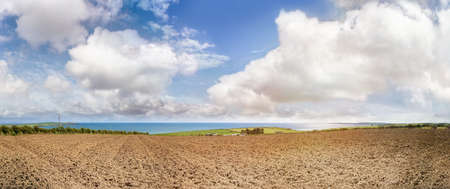 Panoramic landscape with plowed soil in spring. South west of Ireland.