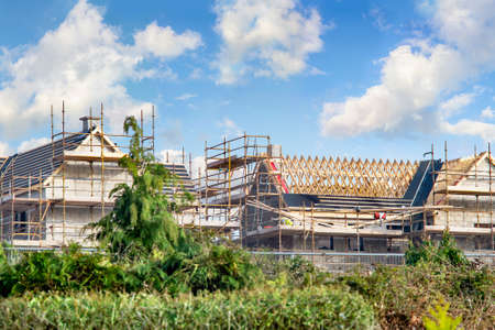 Houses construction with rafters and scaffoldings on cloudy day. Ireland.