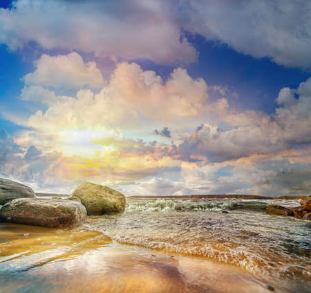 Colorful panoramic landscape with stones and waves at the lake shore on sunset. Lithuania. Kauno marios. Archivio Fotografico
