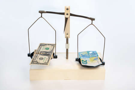 Mechanical scales on which plates put euros and dollars on a white background. Close up. Imagens