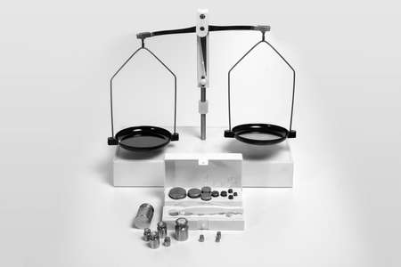 Empty mechanical scales  with white box with weights in front on a white background. Close up.