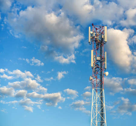 Communication tower with antennas on cloudy sky background.