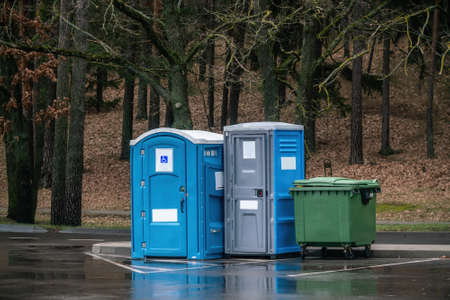 Two portable toilets in a park. One of them for disabled.