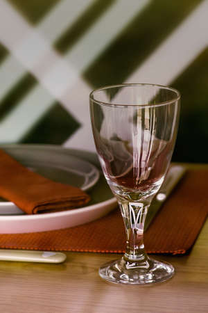 Empty wineglass on the table with plates. Close up. 写真素材
