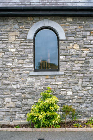 Arch window on the stone wall of house