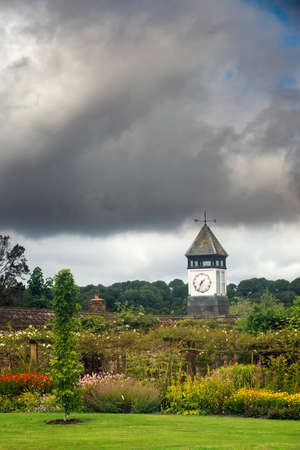 Tower with clock in the garden on cloudy summer day. Stock Photo