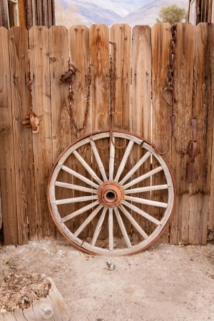 Broken wagon wheel resting against a wooden fence