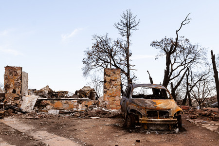 The charred remains of a house and car after a devastating forest fire Stock fotó